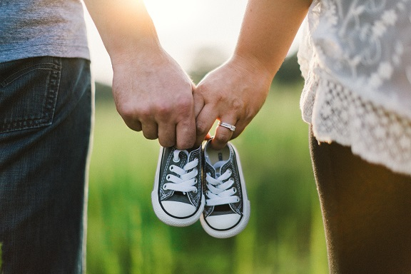 Couple with baby shoes
